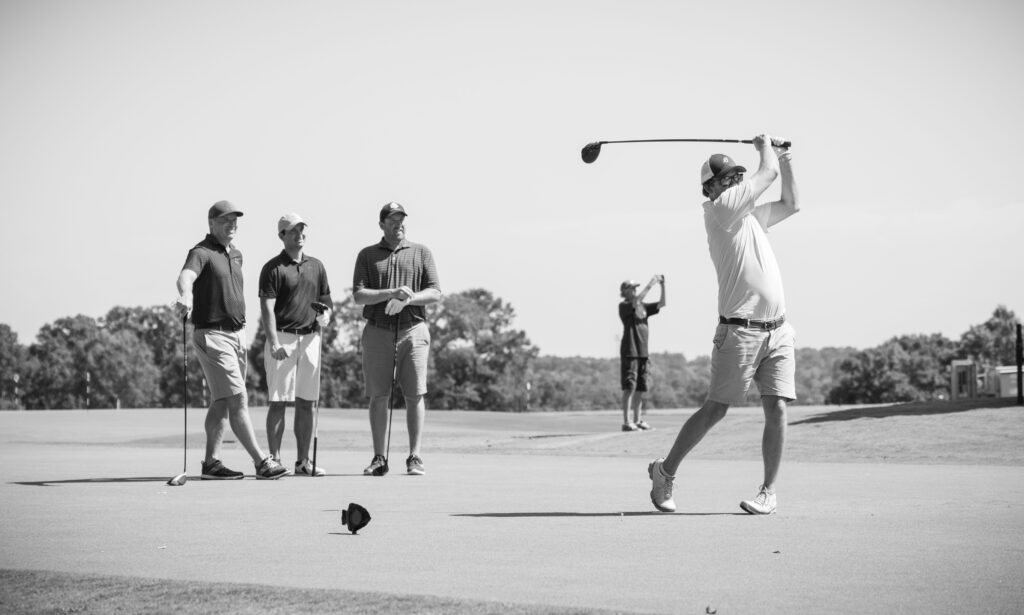 Photo of golf team watching teammate swing club by Atlanta event photographer William Twitty.